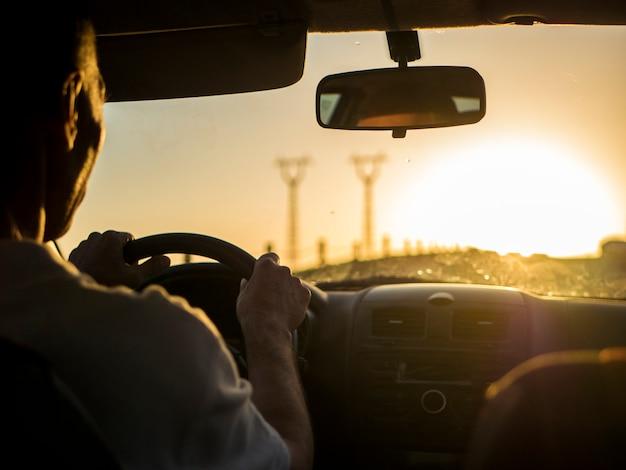 Sluit omhoog silhouet van de mens die een auto op een zonsondergang drijven tijdens gouden uur Premium Foto