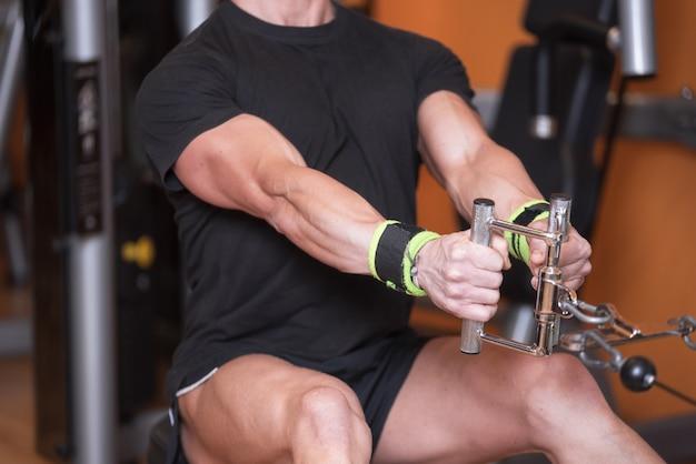 Sluit omhoog sterke mens opleiding in dorsale hoogste trein van de gymnastiek. Premium Foto