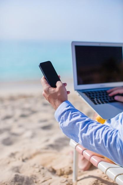 Sluit omhoog telefoon en laptop bij het strand. werken vanaf de kust Premium Foto