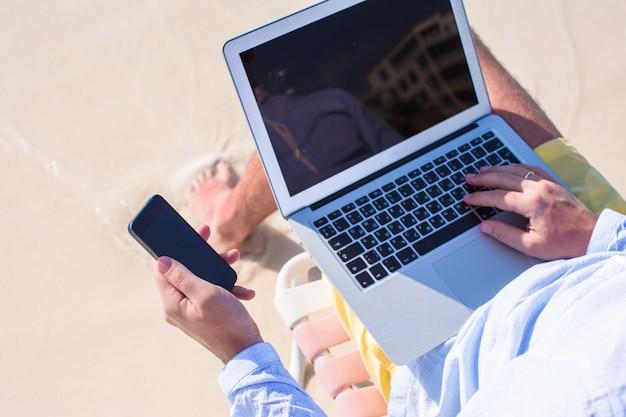 Sluit omhoog telefoon en laptop bij het strand Premium Foto
