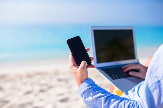Sluit omhoog telefoon op achtergrond van computer bij het strand Premium Foto