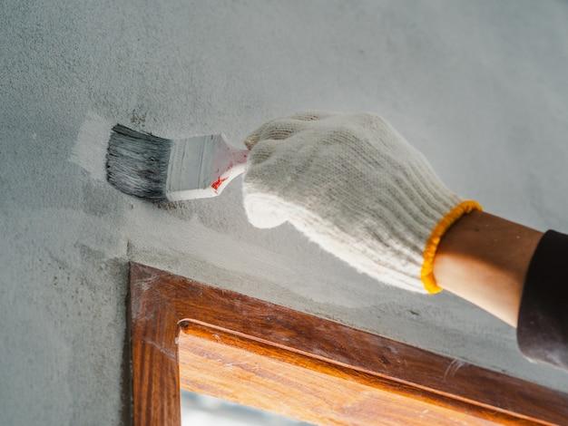 Sluit omhoog van arbeidershand gebruikende rol en borstel voor het schilderen van muur. woningbouw concept. Premium Foto