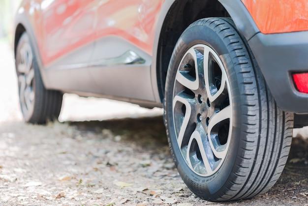 Sluit omhoog van autobanden. achteraanzicht van een geparkeerde auto over een weg bedekt met herfstbladeren. Premium Foto
