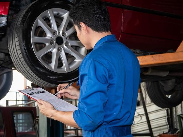 Sluit omhoog van automonteur in het document van het eenvormige holdingscontract. Premium Foto
