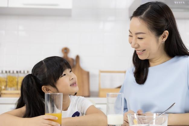 Sluit omhoog van aziatisch familie het drinken jus d'orange Premium Foto