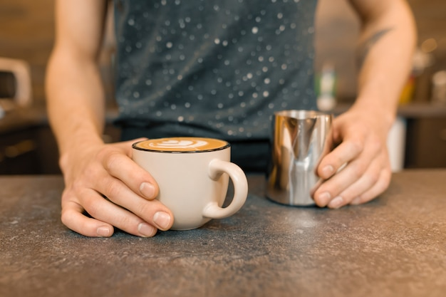 Sluit omhoog van barista'shanden en vers voorbereide kunstkoffie met schuim en patroon Premium Foto