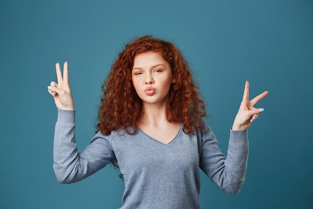 Sluit omhoog van blije jonge vrouw met golvend rood haar en sproeten met vredesgebaar op beide handen, makend eendlippen stellend voor foto op partij. Gratis Foto