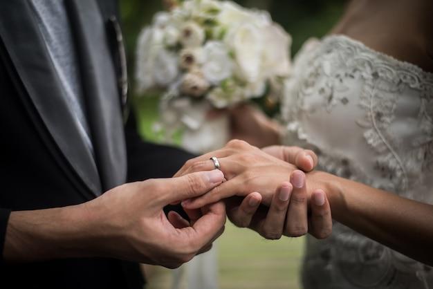Sluit omhoog van bruidegom draagt de ringsbruid in huwelijksdag. liefde, gelukkig huwelijkconcept. Gratis Foto