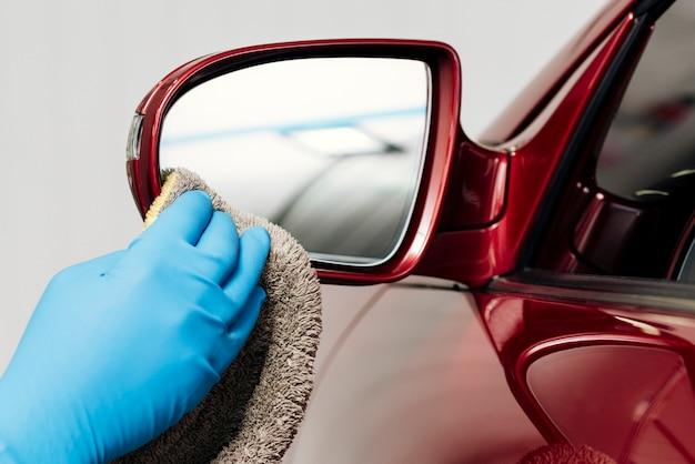 Sluit omhoog van buitenkant van de persoon de schoonmakende auto Gratis Foto