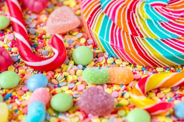 Sluit omhoog van candycane en lolly op een kleurrijke snoepjesachtergrond Gratis Foto