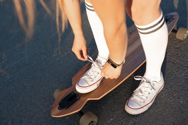 Sluit omhoog van damebeen in witte tennisschoenen die na extreme grappige rit rusten haar houten longboardskateboard. moderne stedelijke hipster meisje veel plezier. goede zonnige zomerdag om te skateboarden en plezier te hebben Premium Foto