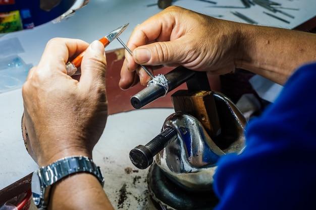 Sluit omhoog van de hand die van een goudsmid zilveren ring maakt. Premium Foto