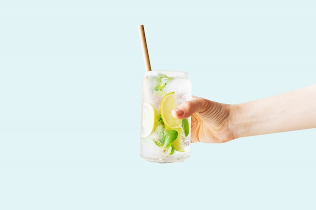 Sluit omhoog van de hand van een vrouw houdend een glas van tropische mojitococktail Premium Foto