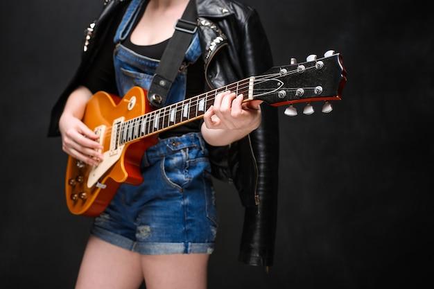 Sluit omhoog van de handen van het meisje op gitaar over zwarte achtergrond. Gratis Foto