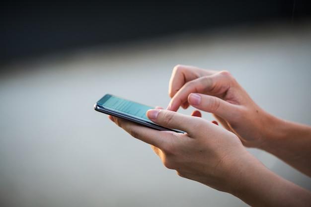 Sluit omhoog van de handen van vrouwen houdend celtelefoon met het lege scherm voor tekstbericht of promotieinhoud Premium Foto