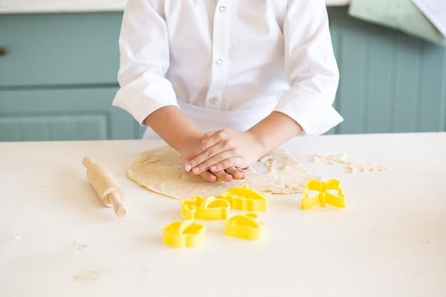 Sluit omhoog van de koekjes van het jongensbaksel in keuken Premium Foto