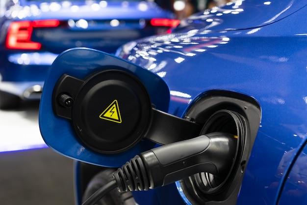 Sluit omhoog van de levering van de machtskabel belastend een elektrische auto. Premium Foto