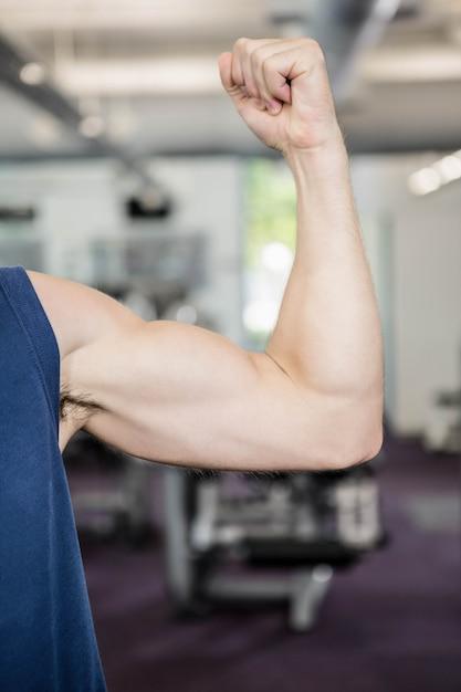 Sluit omhoog van de mens die bicepsen toont bij de gymnastiek Premium Foto