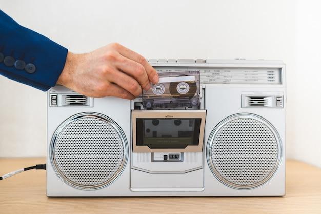 Sluit omhoog van de mens gebruikend een oude radio binnen. Premium Foto