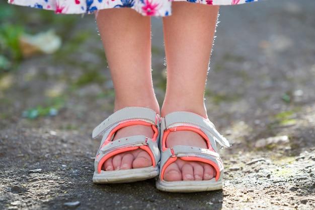 Sluit omhoog van de voeten van het kindmeisje die de schoenen van de zomersandals dragen Premium Foto