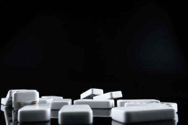 Sluit omhoog van dominostukken op zwarte achtergrond Premium Foto