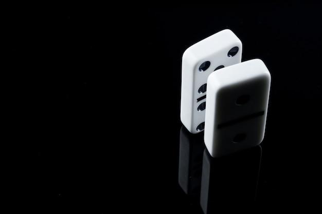 Sluit omhoog van dominostukken op zwarte oppervlakte Premium Foto