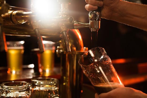 Sluit omhoog van een barman gietend bier Gratis Foto