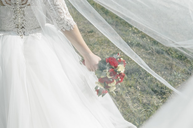 Sluit omhoog van een bruid die een huwelijksboeket met rode en witte rozen houdt. Premium Foto