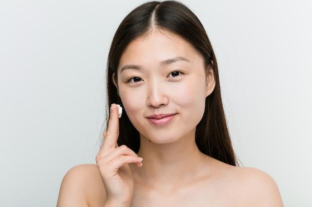 Sluit omhoog van een jonge mooie en natuurlijke aziatische vrouw die een bevochtigende room toepast Premium Foto