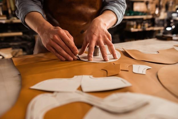 Sluit omhoog van een mannelijke textiel van het schoenmakers scherpe leer Gratis Foto