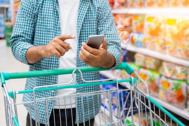 Sluit omhoog van een mens gebruikend smartphone en winkelend in een supermarkt, het winkelen concept Premium Foto
