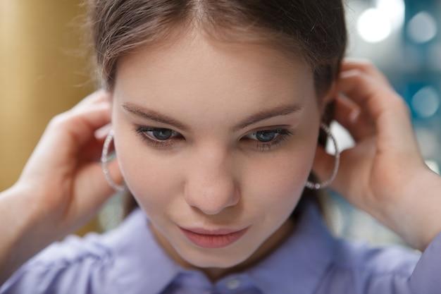 Sluit omhoog van een mooie vrouw die hoepeloorringen draagt, haar haar aanraakt Premium Foto