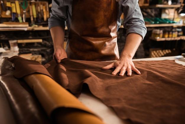 Sluit omhoog van een schoenmaker die met leertextiel werkt Gratis Foto