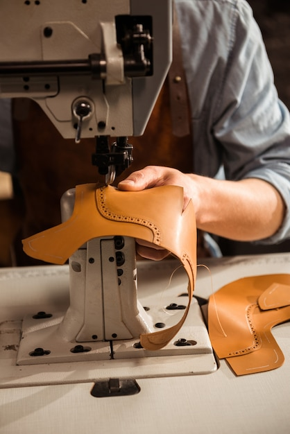 Sluit omhoog van een schoenmaker gebruikend naaimachine Gratis Foto