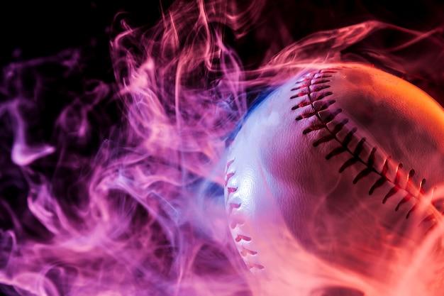 Sluit omhoog van een witte honkbalbal in multi-coloured rode rook van een vape op een zwarte geïsoleerde achtergrond Premium Foto