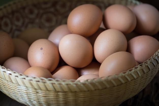 Sluit omhoog van eieren in een mand op houten lijstachtergrond Premium Foto