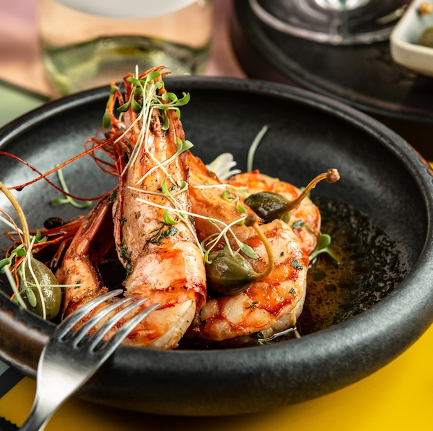 Sluit omhoog van gebraden garnalen die met groenten in het zuur en verse kruiden worden versierd Gratis Foto