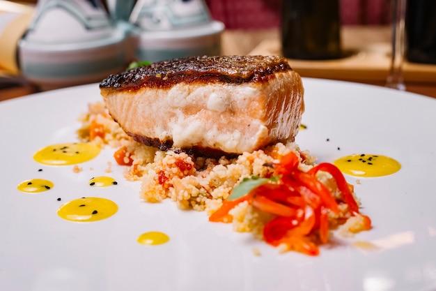 Sluit omhoog van geroosterd visfilet dat bovenop de kouskoussalade wordt gediend met groene paprika's Gratis Foto