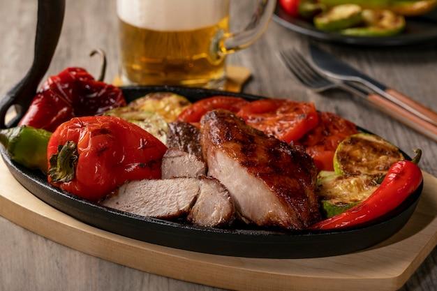 Sluit omhoog van geroosterd vlees op gietijzerpan met geroosterde groenten op rustieke houten lijst. Premium Foto