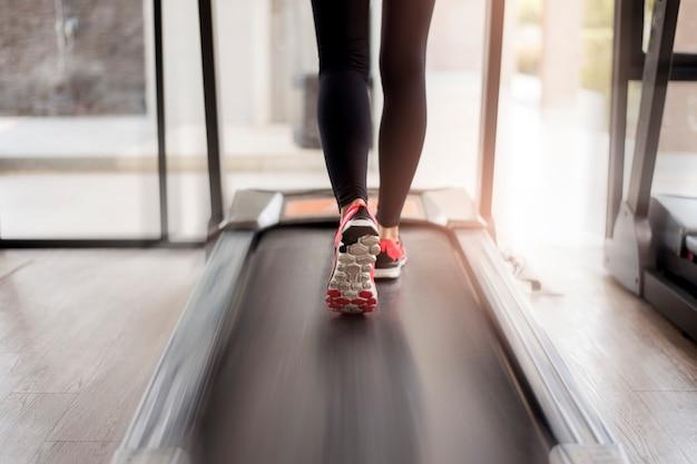 Sluit omhoog van gespierde de benenvoeten die van de vrouw op tredmolentraining lopen bij fitness gymnastiek Premium Foto