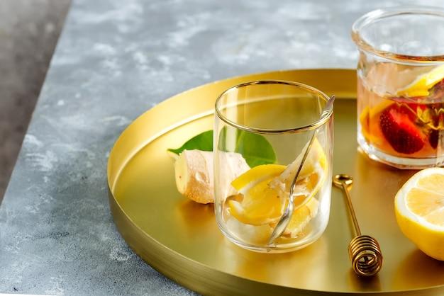 Sluit omhoog van gezonde ingrediënten voor gember, citroen en honingthee op een koperen dienblad Premium Foto