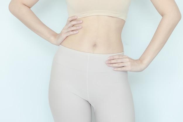 Sluit omhoog van gezonde vrouw toon slank lichaam Premium Foto