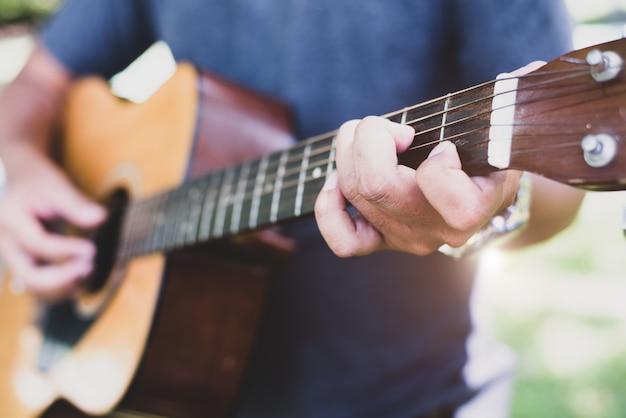 Sluit omhoog van gitaristhand het spelen gitaar. muzikaal en instrument concept Premium Foto