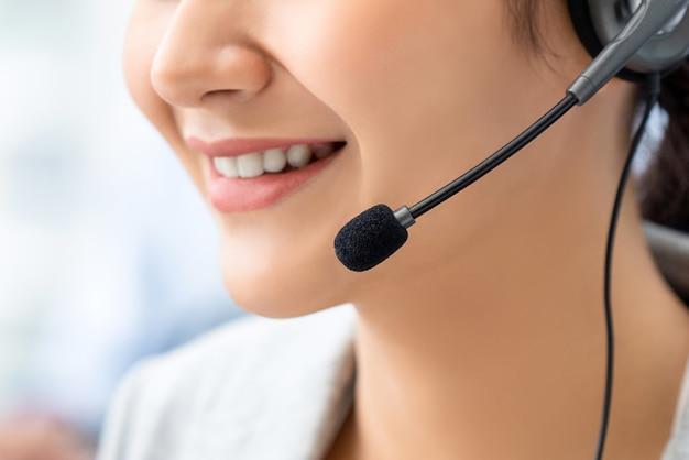 Sluit omhoog van glimlachende vrouwenopertor in call centre Premium Foto