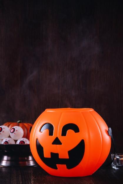 Sluit omhoog van griezelige halloween-trucs, concept het decor van het horrorfestival, pompoenlantaarn met kandelaar en rook. Premium Foto