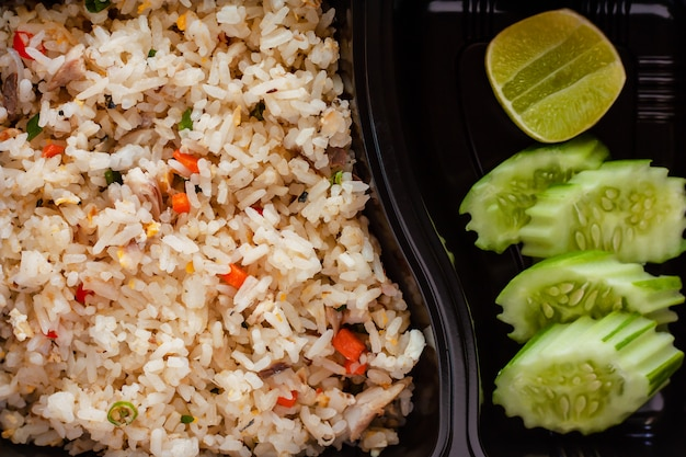 Sluit omhoog van heerlijke gebraden rijst met komkommer en citroen aan kant in lunchdoos Premium Foto