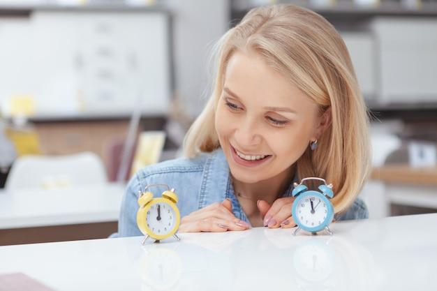 Sluit omhoog van het gelukkige mooie vrouw glimlachen, bekijkend aanbiddelijke kleine wekker op de lijst Premium Foto