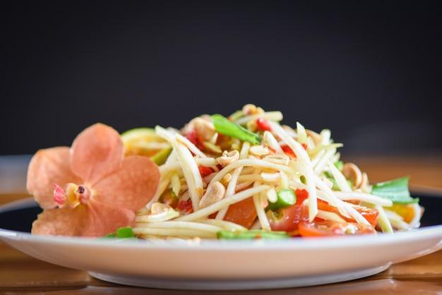 Sluit omhoog van het groene kruidige thaise voedsel van de papajasalade op de lijst selectieve nadruk - som tum thais aziatisch voedsel - papajasalade die op plaat wordt gediend Premium Foto
