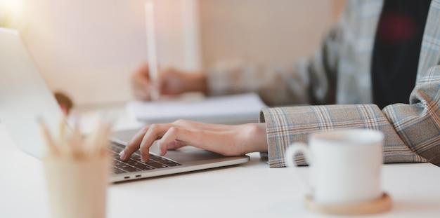 Sluit omhoog van het jonge onderneemster typen op laptop computer Premium Foto
