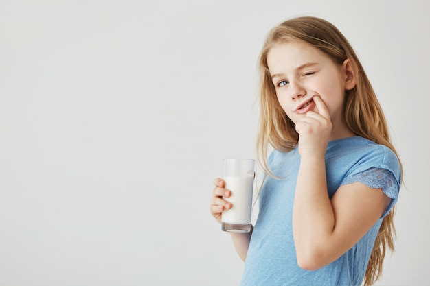 Sluit omhoog van het leuke meisje met blauwe ogen kijkt opzij, drinkend glas melk en schoonmakende tanden na een maaltijd met vinger. zorgeloze jeugd. Gratis Foto